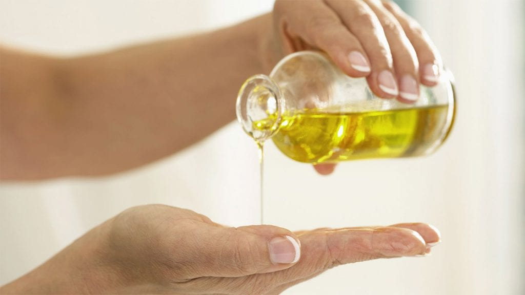 Oil Being Poured On Hand